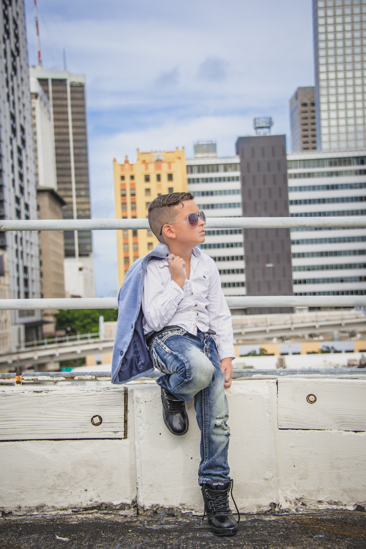boy holding jacket posing like model on a rooftop