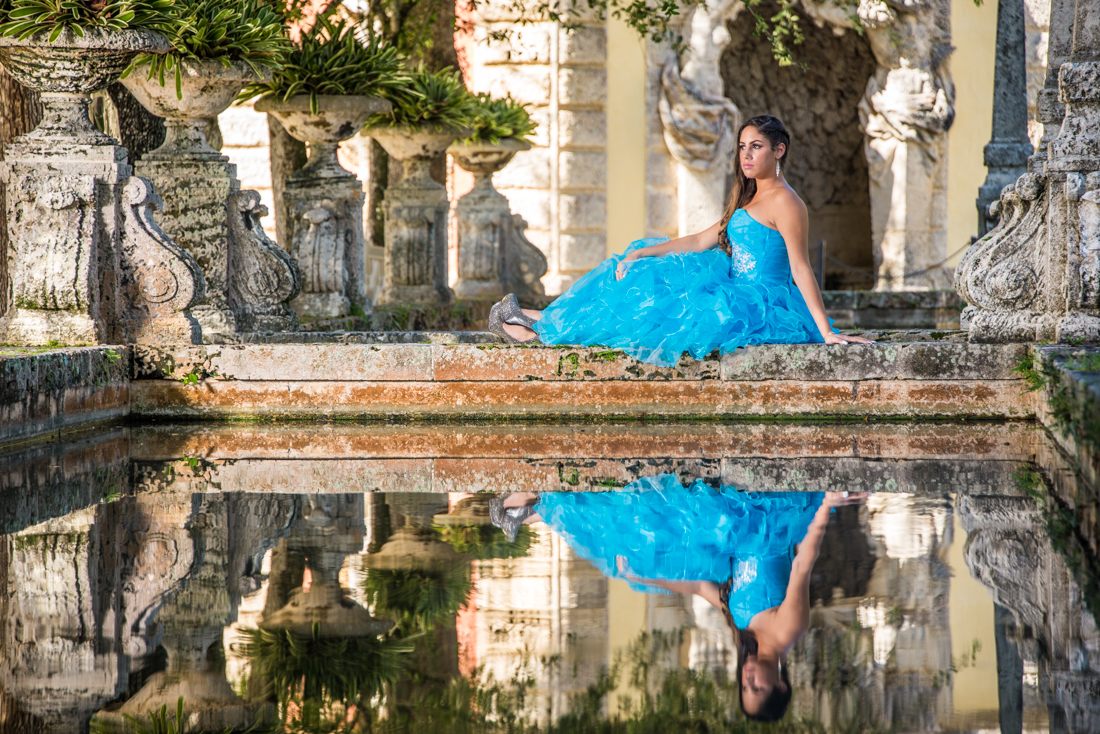 Quinceañera on blue dress reflecting on water at Vizcaya museum