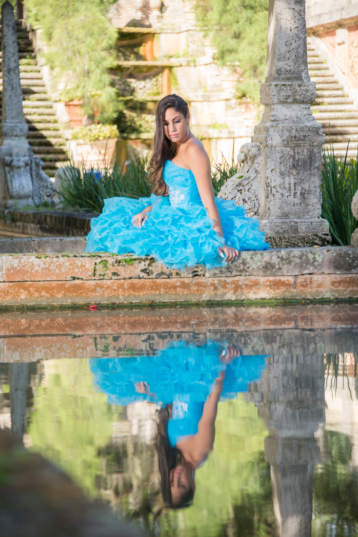 Quinceañera on blue dress reflecting on water at Vizcaya Museum.