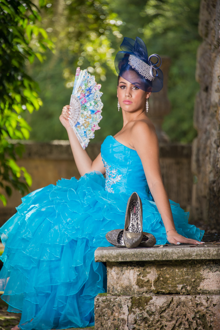 Quinceañera sitting next to her shoes with blue dress and hat using a fan