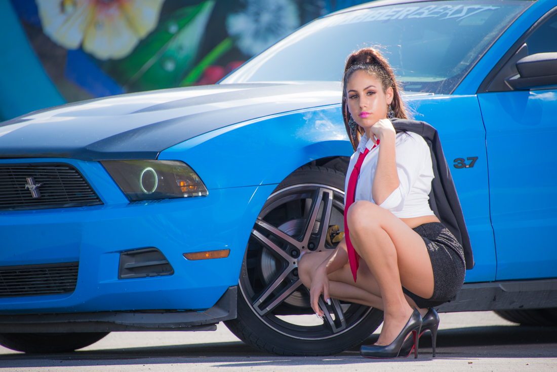 Quinceañera holding jacket next to Mustang