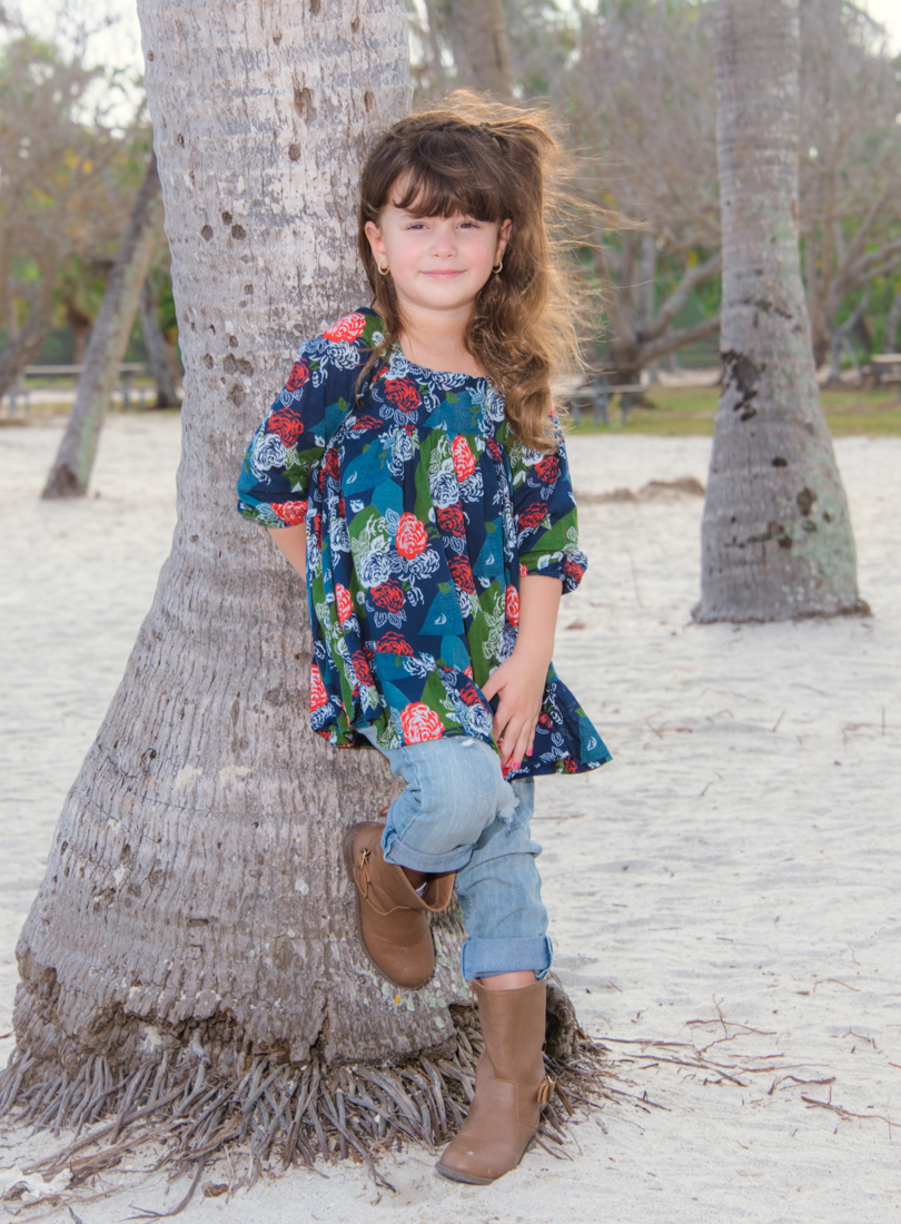 girl leaning on palm tree at beach picture