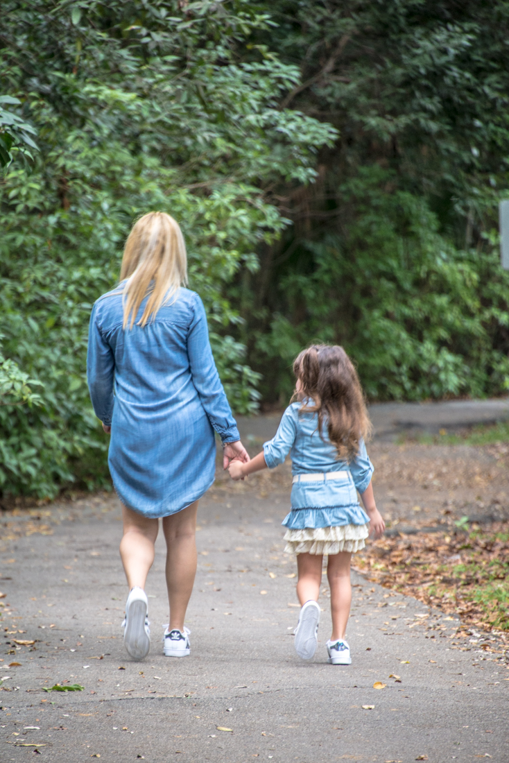 mom and daughter walking away holding hands