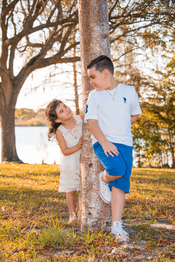 brother and sister at park leaning on tree